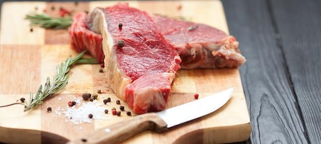 Filete crudo ase a la parrilla rib eye steak o filete de grupa en la tabla rústica con romero.