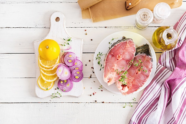 Filete crudo de carpa pescado con limón y tomillo. preparar pescado para asar en papel pergamino. vista superior. lay flat