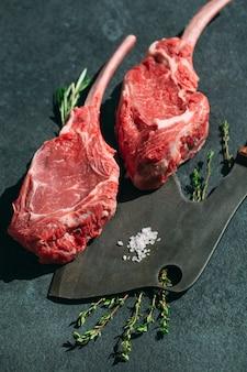 Filete crudo con un cuchillo de carnicero en piedra oscura.