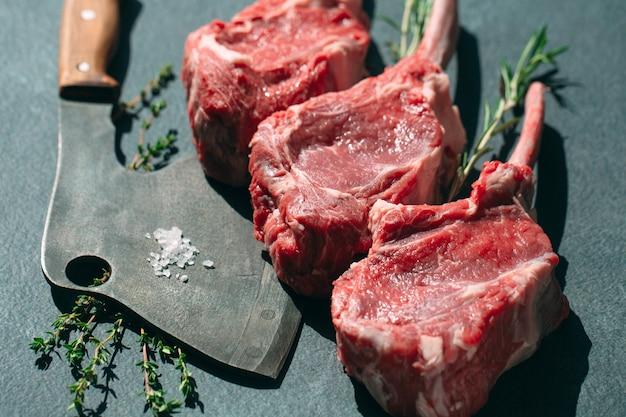 Filete crudo con un cuchillo de carnicero sobre una superficie de piedra oscura.