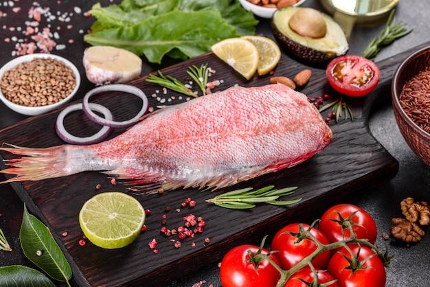 Filete crudo de perca del mar rojo preparado para hornear con especias y hierbas