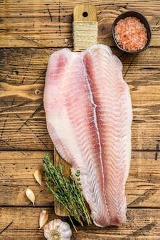 Filete crudo de pescado pangasius sobre una tabla para cortar.
