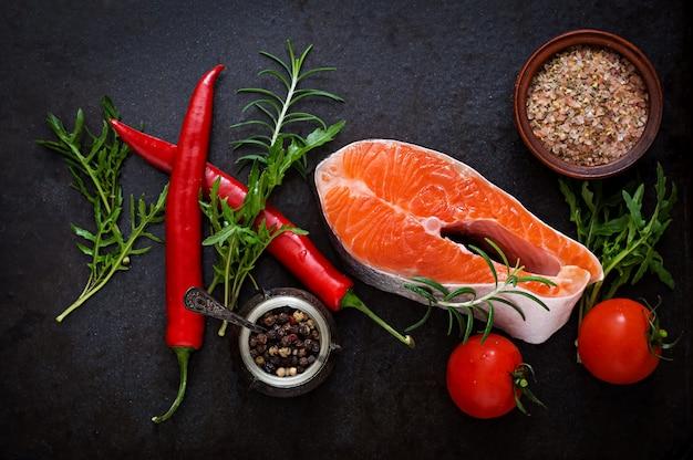Filete crudo salmón y verduras para cocinar en una mesa negra. vista superior