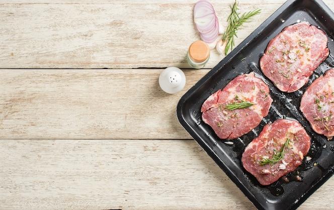 Filete de carne fresca cruda con hojas de romero y sal en una bandeja negra listo para cocinar, vista superior