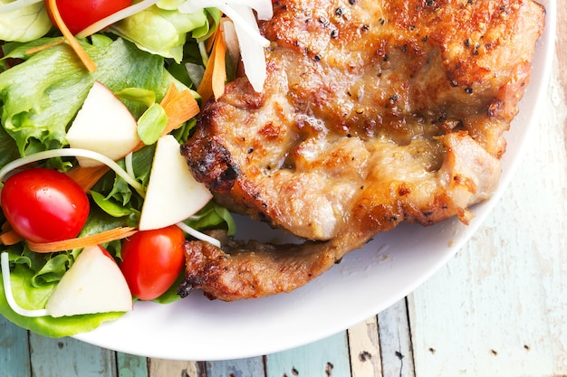 Filete de chuleta de cerdo a la pimienta negra con ensalada.