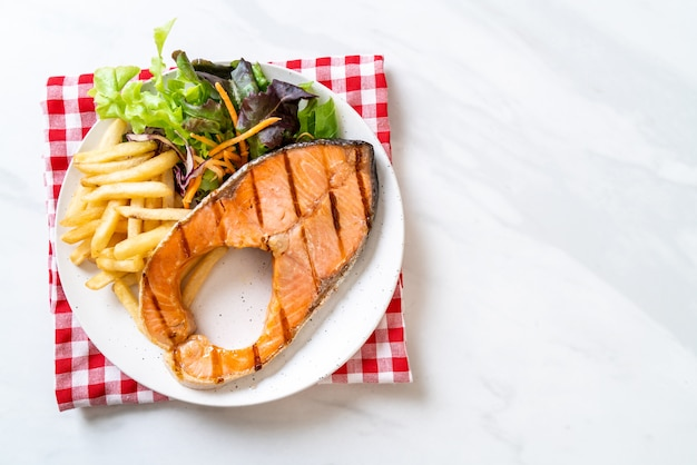 Filete de filete de salmón a la parrilla con vegetales y papas fritas