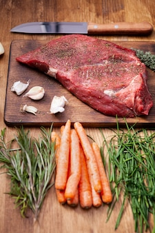 Filete grande de carne roja sobre tabla de cortar rústica junto a verduras frescas y cuchillo de chef. hierbas verdes.