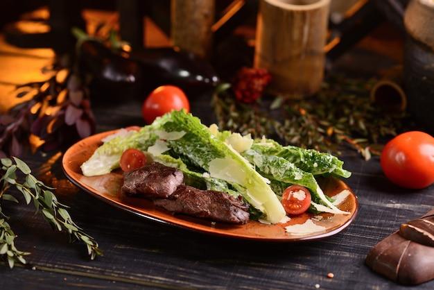 Filete con lechuga, parmesano y tomates cherry. en un plato rojo sobre una mesa de madera oscura.