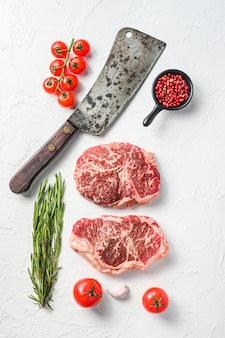 Filete de lomo crudo, carne orgánica con condimentos, romero y cuchillo de carnicero. fondo de textura blanca. vista superior.