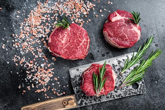 Filete mignon solomillo de carne cruda filetes de ternera en la mesa de carnicería. fondo negro. vista superior.