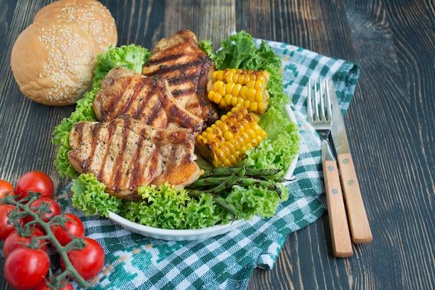 Filete a la parrilla en un recipiente redondo con especias, hierbas y verduras sobre un fondo oscuro de la madera. platos con carne. fondo de madera oscura copia espacio