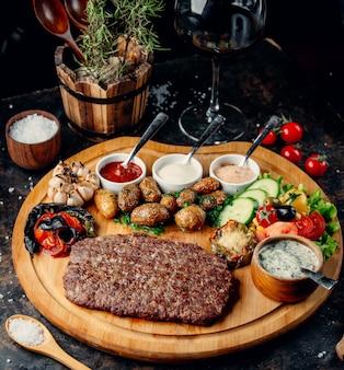 Filete con patatas y verduras sobre tabla de madera