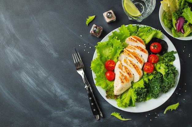 Filete de pechuga de pollo y ensalada de verduras con tomates y hojas verdes. el concepto de comida sana y dieta cetogénica. vista superior.