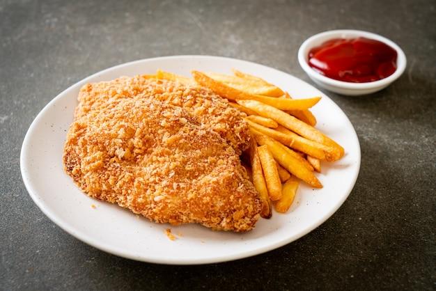 Filete de pechuga de pollo frito con papas fritas y salsa de tomate
