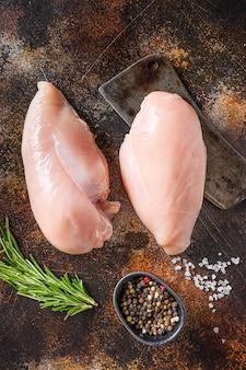 Filete de pechuga de pollo de granja, en la cuchilla de carne, especias y hierbas en la vista superior de la mesa de metal rústico antiguo.