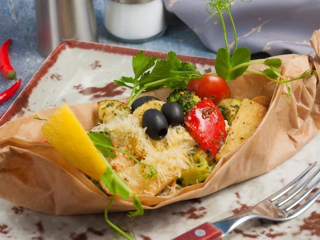 Filete de pescado blanco al horno en pergamino con verduras y queso