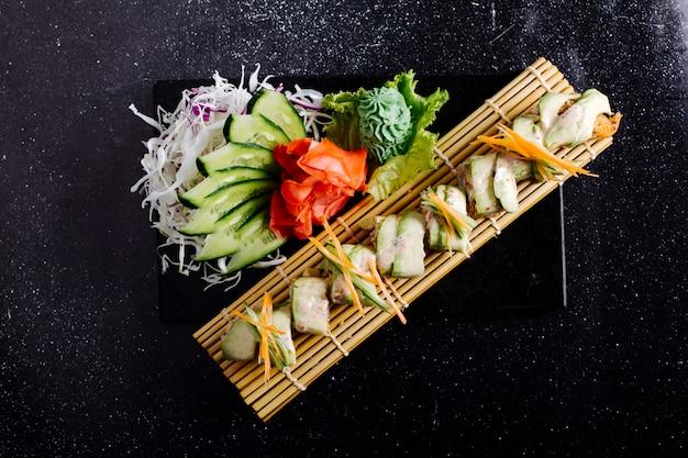 Filete de pescado blanco sobre estera de sushi con jengibre, wasabi y pepino en mesa negra.