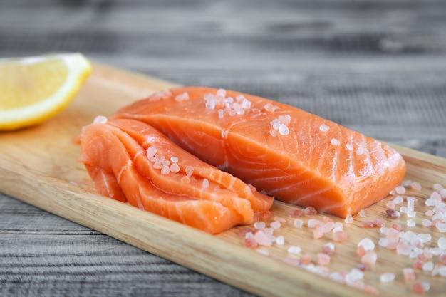 Filete de pescado crudo fresco de salmón sobre tabla de cortar de madera