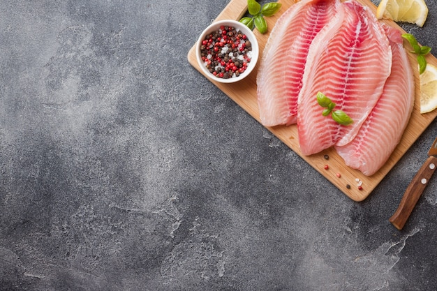 Filete de pescado crudo de tilapia en una tabla de cortar con limón y especias. mesa oscura con espacio de copia.