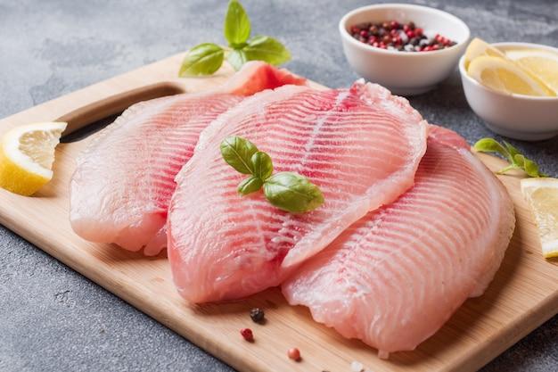 Filete de pescado crudo de tilapia en una tabla de cortar con limón y especias. mesa oscura