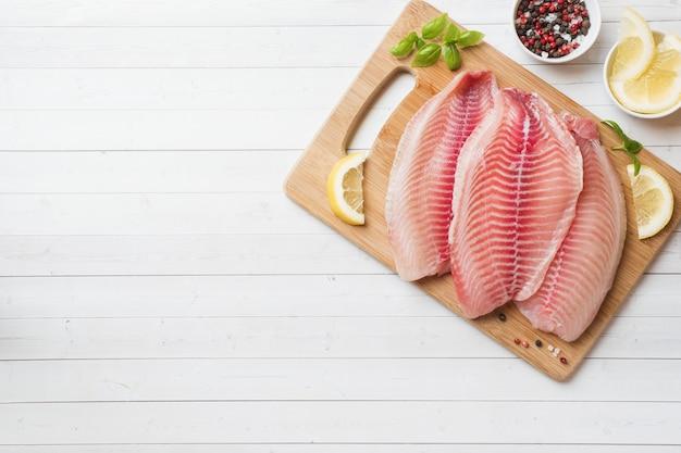Filete de pescado crudo de tilapia en una tabla para cortar con limón y especias
