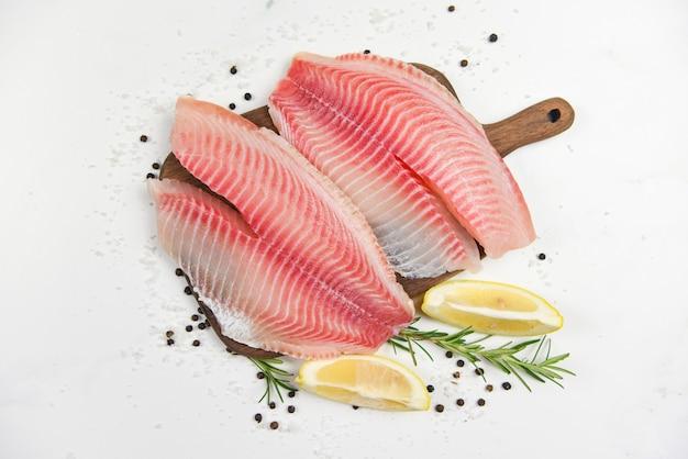 Filete de pescado fresco en rodajas para filete o ensalada con hierbas especias romero y limón - filete de tilapia crudo pescado y sal sobre fondo de piedra blanca e ingredientes para cocinar alimentos
