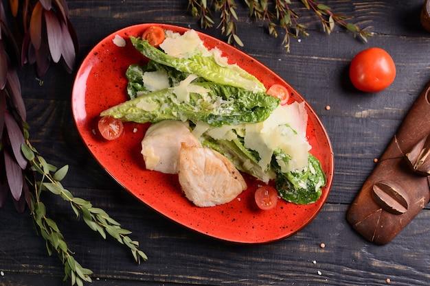 Filete de pescado frito con lechuga, tomates cherry y parmesano. en un plato rojo