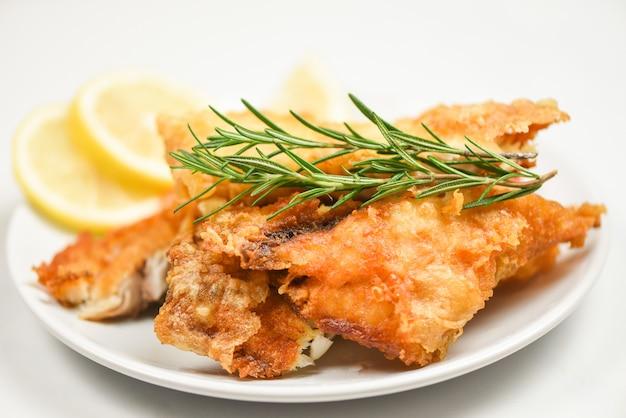 Filete de pescado frito en rodajas para filete o ensalada cocinar alimentos con hierbas especias romero y limón - filete de tilapia crujiente de pescado servido en plato blanco