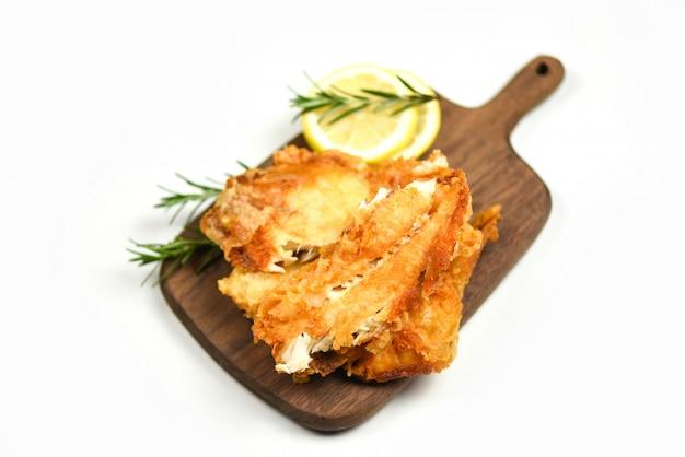 Filete de pescado frito en rodajas para filete o ensalada cocinar alimentos con hierbas especias romero y limón tilapia filete de pescado crujiente servido sobre tabla de cortar de madera y fondo blanco.