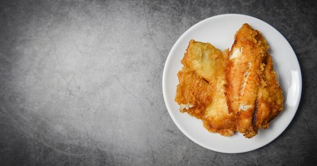 Filete de pescado frito en rodajas para filete o ensalada para cocinar, vista superior copia espacio - filete de tilapia crujiente de pescado servido en plato blanco