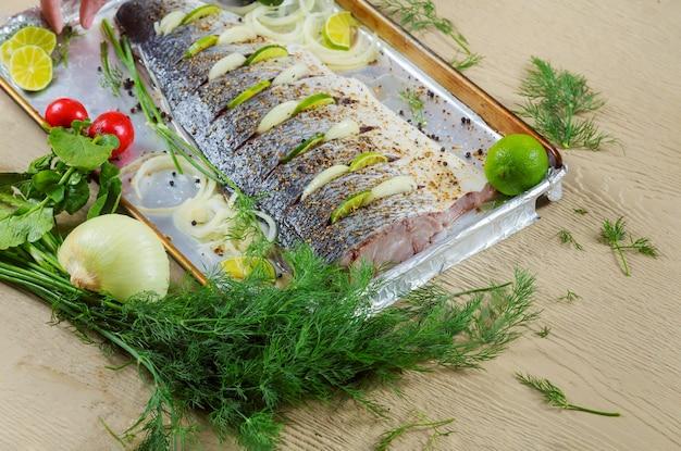 El filete de pescado marinado se prepara para hornear en el horno sobre el filete con cebolla