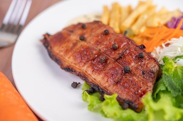 Filete de pescado con papas fritas, kiwi, lechuga, zanahorias, tomates y repollo en un plato blanco.