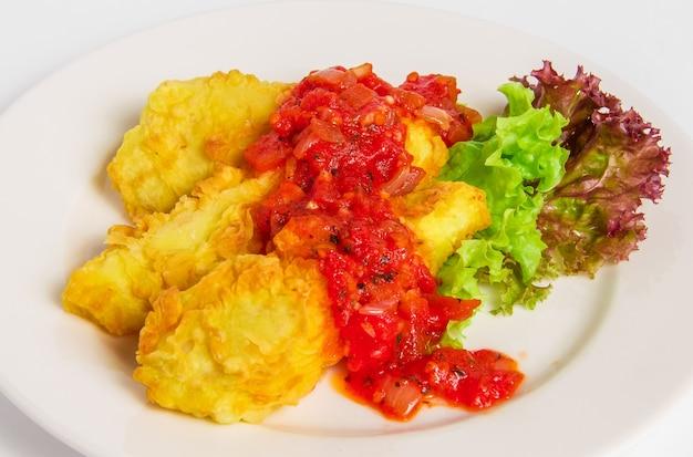 Filete de pescado rebozado frito en plato blanco