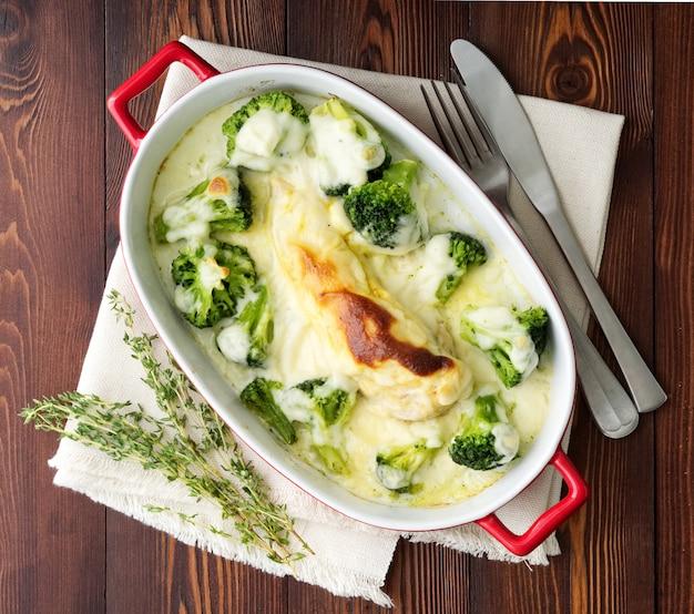 Filete de pollo al horno con brócoli en salsa bechamel en mesa de madera oscura.