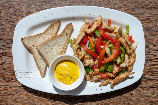 Filete de pollo asado con verduras y pan en un plato blanco, primer plano