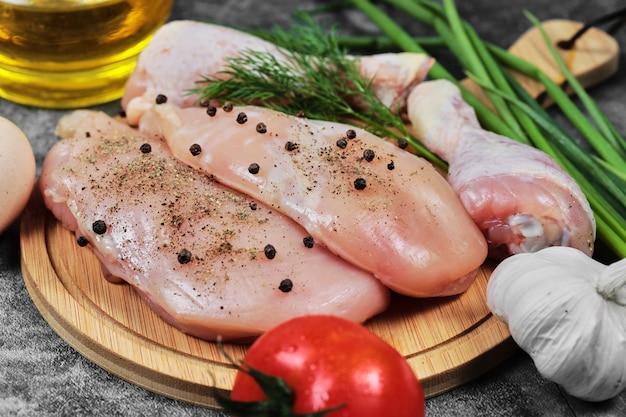 Filete de pollo crudo y piernas en placa de madera con verduras frescas.