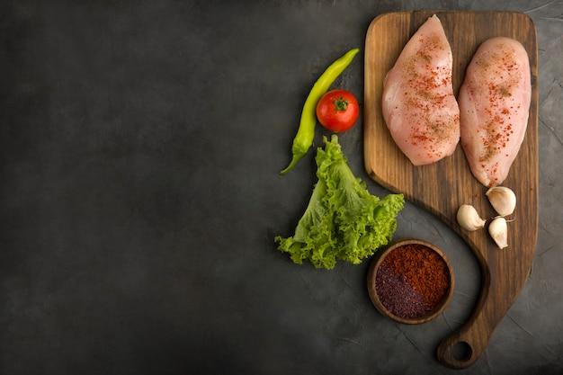 Filete de pollo crudo servido con verduras y salsas