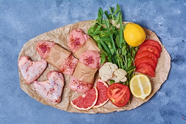 Filete de pollo crudo con verduras sobre una tabla de madera en azul
