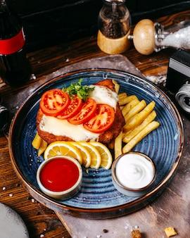 Filete de pollo empanado frito con queso servido con rodajas de tomates, limones y papas fritas
