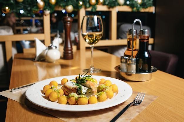 Filete de pollo con espinacas y ñoquis en un plato blanco sobre una mesa en un restaurante.