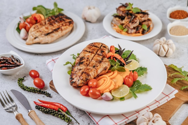 Filete de pollo con limón, tomate, chile y zanahoria en un plato blanco.
