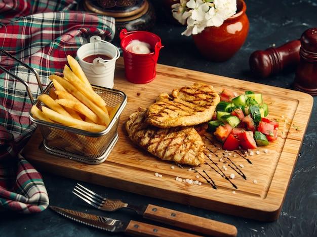 Filete de pollo con papas fritas y ensalada de verduras.