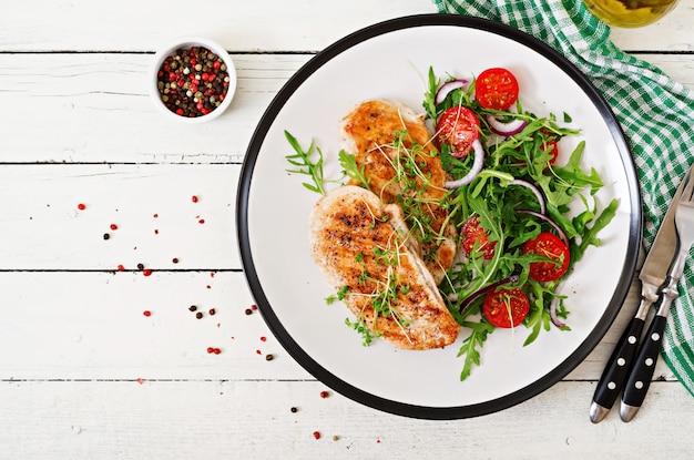Filete de pollo a la parrilla y ensalada de vegetales frescos de tomate, cebolla roja y rúcula. ensalada de carne de pollo. comida sana