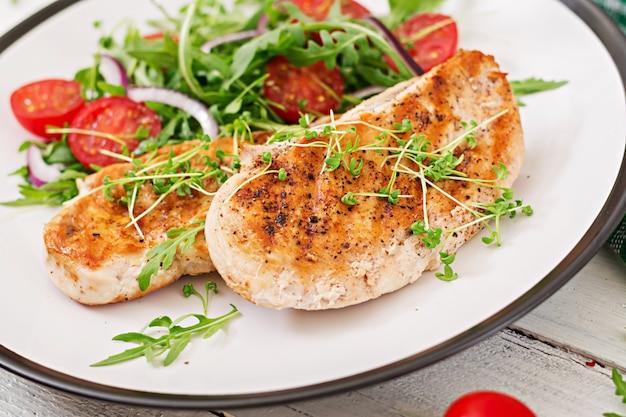 Filete de pollo a la parrilla y ensalada de vegetales frescos de tomate, cebolla roja y rúcula.