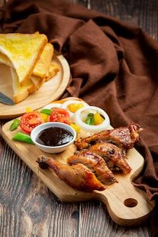 Filete de pollo a la plancha y verduras sobre fondo de madera oscura.