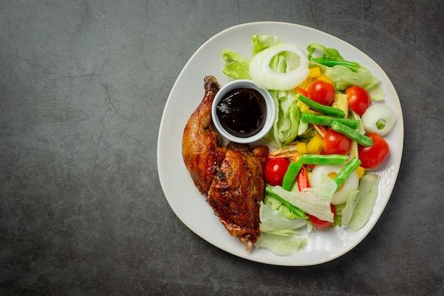 Filete de pollo a la plancha y verduras sobre fondo oscuro