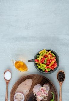 Filete de pollo y verduras en placa de madera con macarrones.