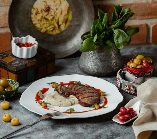 Filete de res finamente cortado servido con guarnición de arroz y salsa de tomate