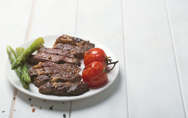 Filete de res a la parrilla en un plato blanco y superficie blanca