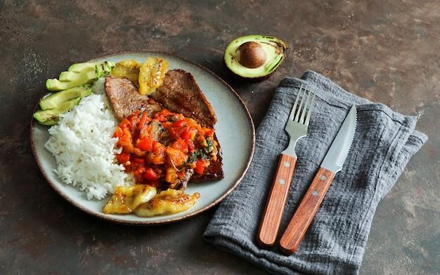 Filete de res con salsa de tomate, arroz, aguacate y papas fritas